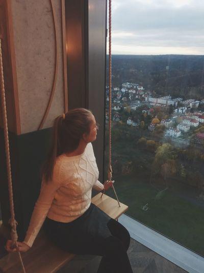 Woman looking through window sitting on swing