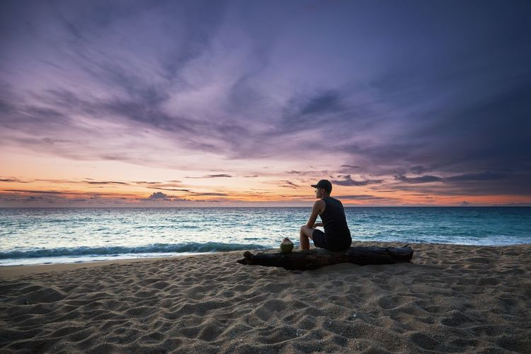Side view of young man sitting on log at beach against sky during sunset