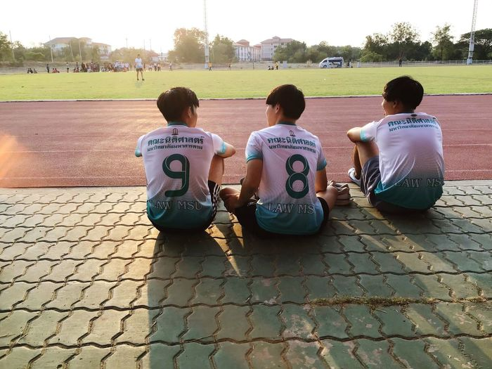 Rear view of players sitting on footpath at playground