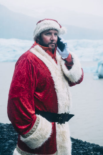 Man in santa costume talking on smart phone while standing by lagoon during winter