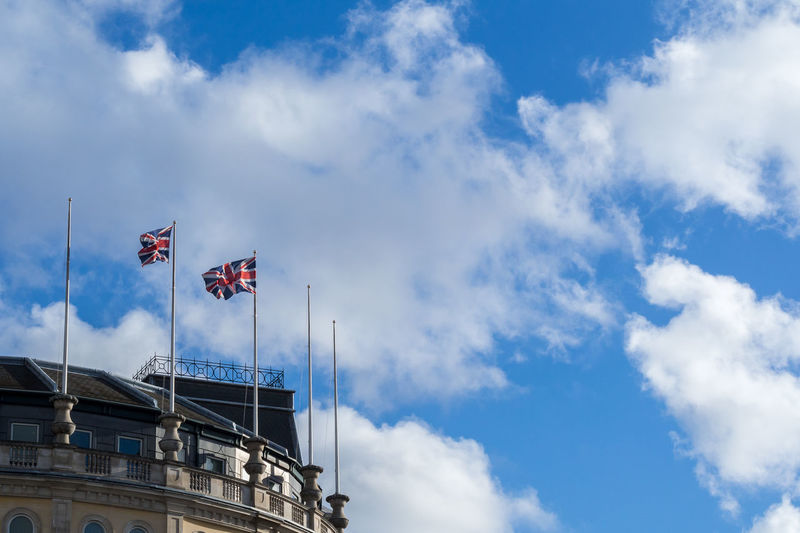 Cropped image of historic building with british flags against sky