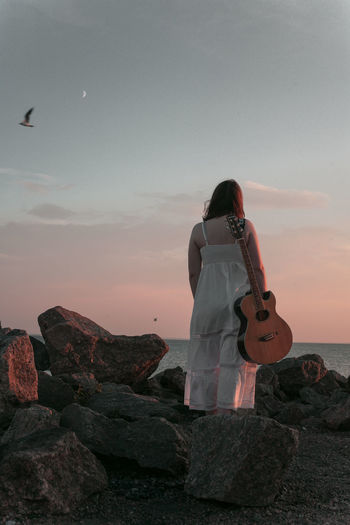 Rear view of woman standing on rock against sky during sunset