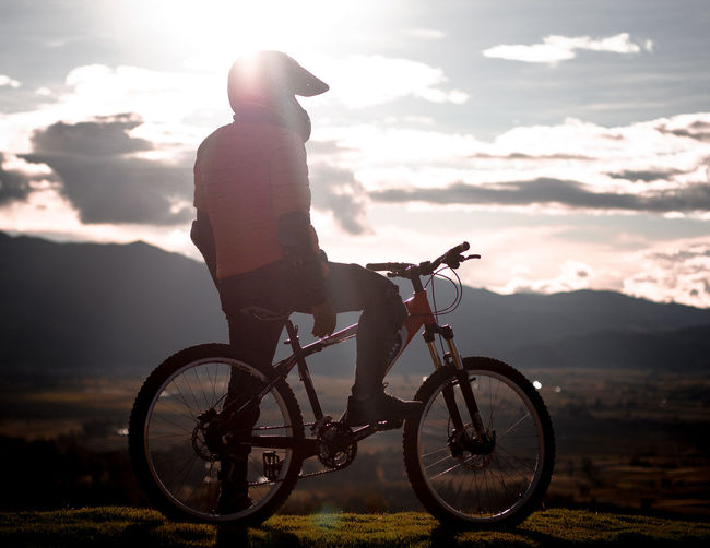 Side view of man riding bicycle against sky during sunset