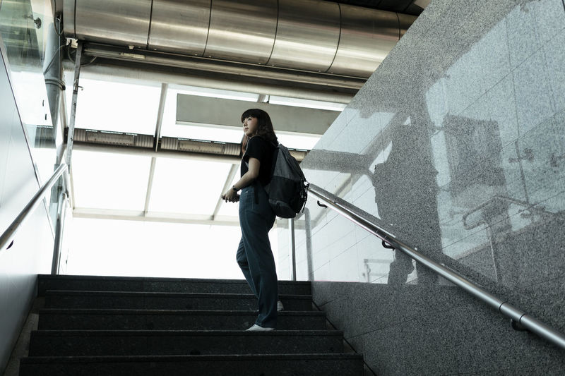 Low angle view of woman walking on staircase in building