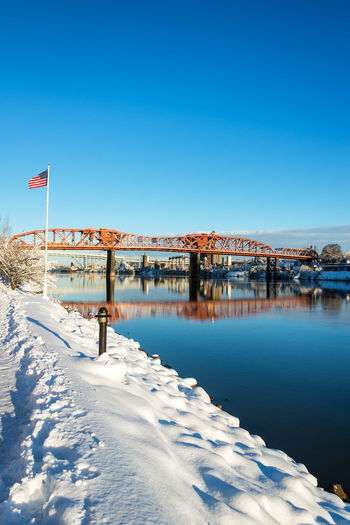 American flag waving in the window in winter with the Broadway Bridge in the background in Portland, Oregon Architecture Bridges Broadway Downtown Ice Mirror Oregon Pacific Portland Reflection Tree Trees Willamette River  Winter Bridge Cold Colorful Icy Northwest Old River Snow Town Waterfront White