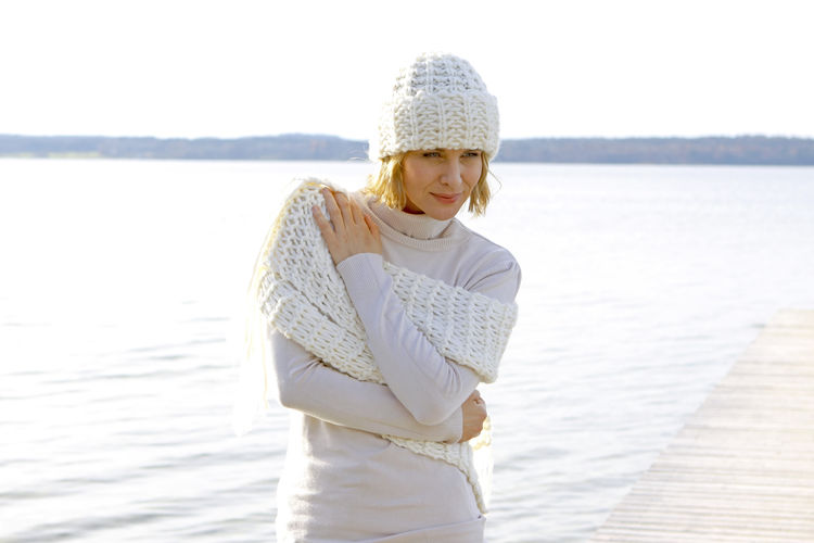 Blonde middle-aged woman on an autumn walk at the lake, portrait Autumn Walk Adult Beauty In Nature Day Front View Knit Hat Lake Lakeside Leisure Leisure Activity Lifestyles Middle Aged Nature One Person Outdoors People Standing Vacations Warm Clothing Water Winter Women Young Adult Young Women