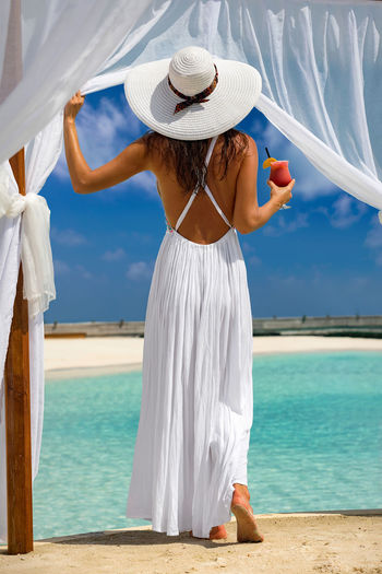 Woman in white dress enjoys the view to a tropical beach with a drink in her hand Cocktail Maldives Tropics Vacations Woman Beach Day Drink Glass Hat Leisure Activity Lifestyles Model One Person Outdoors Rear View Sand Scenics Sea Standing Summer Sun Hat Sunlight Tranquil Scene Water