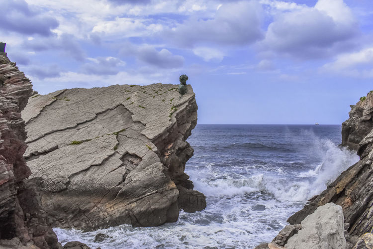 Rock formations on sea shore against sky