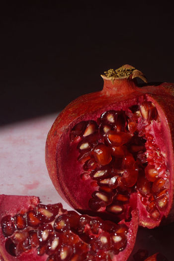 Close up of a pomegranate fruit Pomegranate Fruit Juicy Juice Freshness Fresh Red Red Color Pomegranate Red Fruit Black Background Close-up Halved Pomegranate Seed Seed Served Cross Section