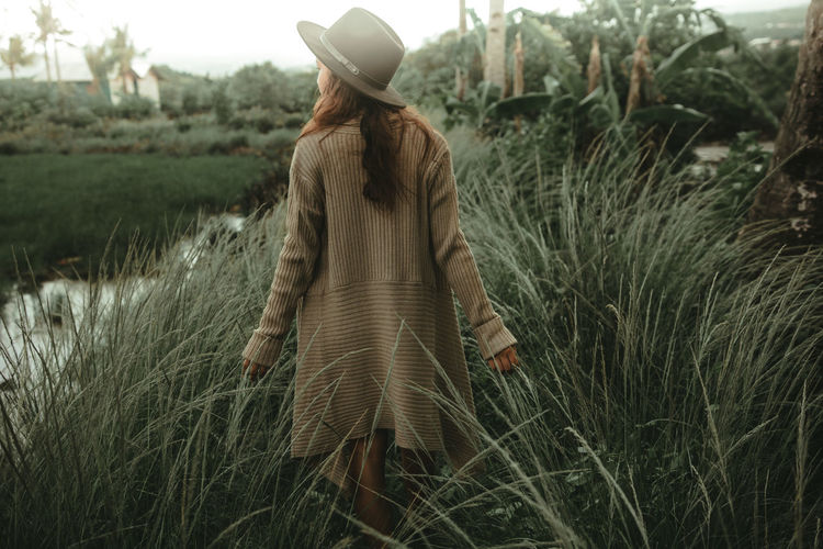 Rear View Of Woman Walking Amidst Grassy Field By Lake At Forest