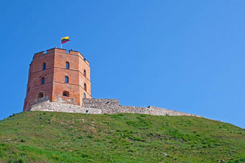Gediminas' Tower or Castle, the remaining part of the Upper Castle in Vilnius, Lithuania with lithuanian flag waving on a green hill and blue sky Baltic Castle Castles Gediminas Gediminas Castle Gediminas Tower Hills Holiday Lithuania Lithuanian Flag Travel Vilnius Architecture Building Building Exterior Built Structure Castle Ruin Day Hill History Lithuanian Flag Medieval Outdoors Sky Tower