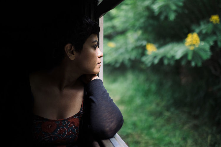 Thoughtful Woman Looking Through Window While Traveling In Train