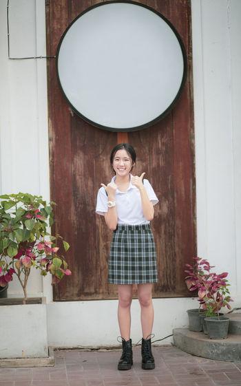 Portrait of smiling girl standing against door