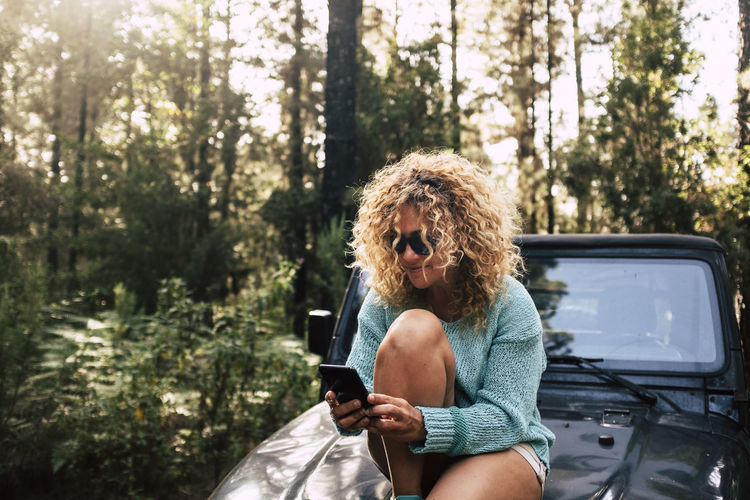 Woman using mobile phone while sitting on vehicle in forest
