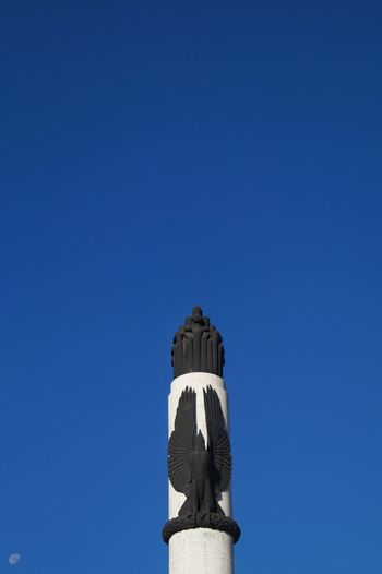 Low angle view of historic statue against clear blue sky