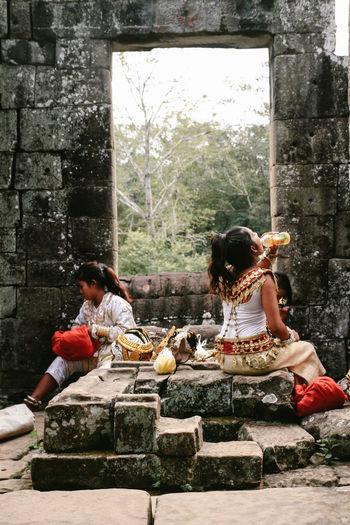 Women sitting on stone wall