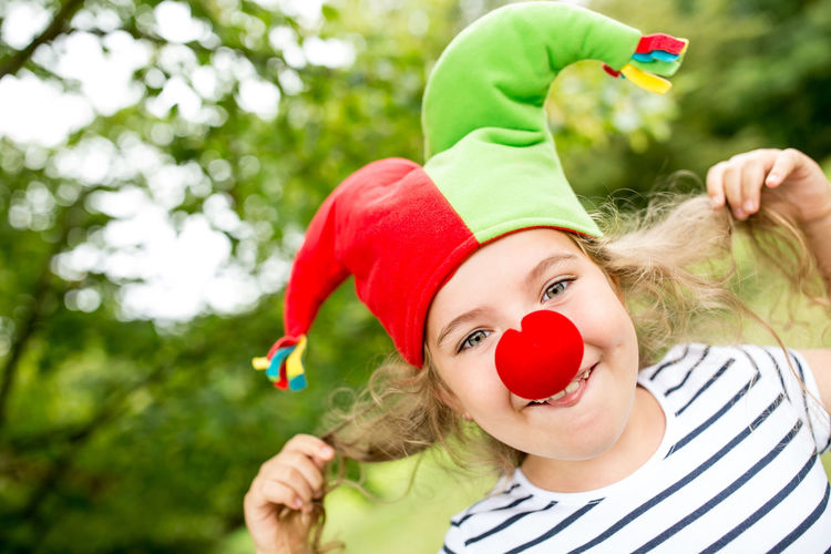 portrait of cute girl with red berries Birthday Braids Cap Carefree Carnival Cheerful Cheerfulness Child Childhood Childrens Birthday Party Clown Colorful Costume Cute Day Dress Up Focus On Foreground Fool  Fool Cap Front View Fun Garden Girl Girls Green Color Happy Headshot Innocence Joy Joyful Laughing Leisure Leisure Activity Lifestyle Lifestyles Luck Merry Nature Nose One Person Outdoors Outside Park Plant Play Portrait Pull Real People Red Silly Spring Summer
