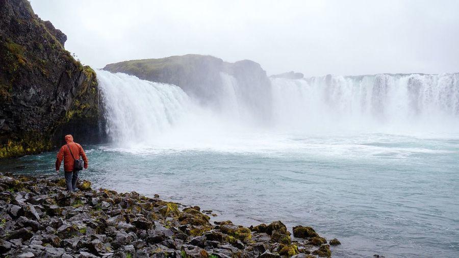 Rear View Of Man Walking On Rock Against Waterfall