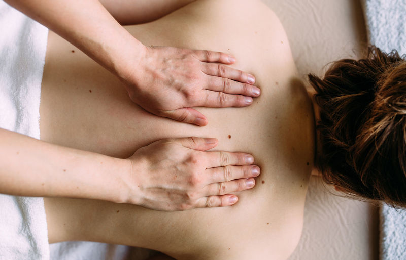Rear view of shirtless woman lying on hand