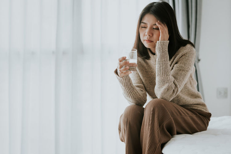 Woman with headache holding glass while sitting on bed at home