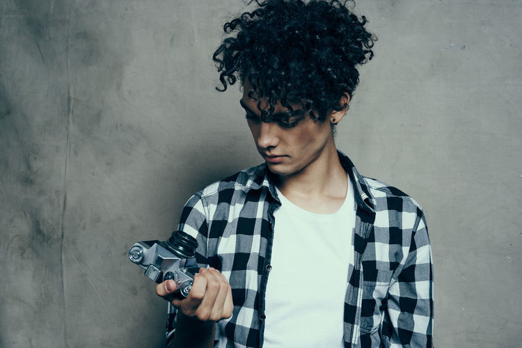 Portrait of young man holding camera against wall
