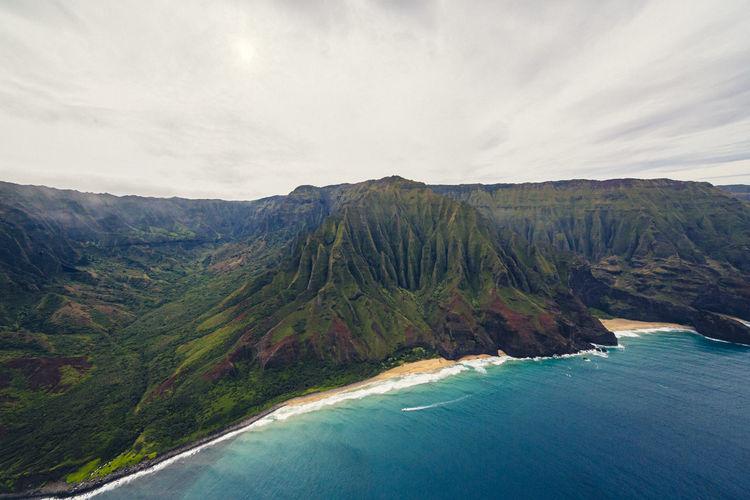 Scenic view of sea and mountains against sky napali coast kauai