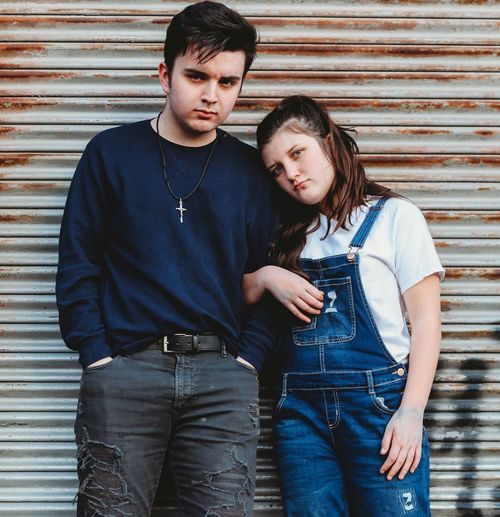 Portrait of young couple standing against wall
