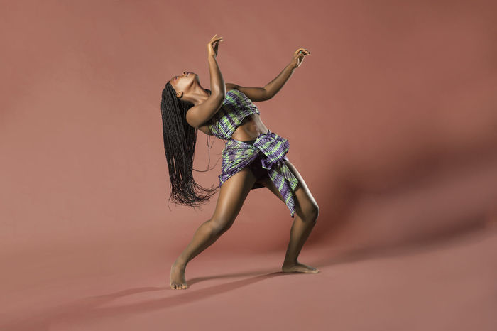 Beautiful African Black girl wearing traditional colorful African outfit does a dramatic dance move against a colorful brown background African African Traditions African Dancer African Woman  Dandelion Tradition Dress