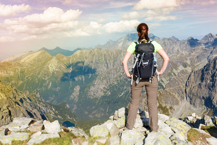 Woman with backpack standing on the edge, looking at mountains (Tatra Mountains Carpathian Mountain Range, Europe) Active Lifestyle  Admiring The View Adventure Backpack Disconnect Disconnected Exploring FAR AWAY Focus On Background Hiking Leisure Activity Lifestyle Lonely Looking Mountain Mountain Range Nature Outdoors Relax Rucksack Tourism Tourist Unplugged Vacation Woman