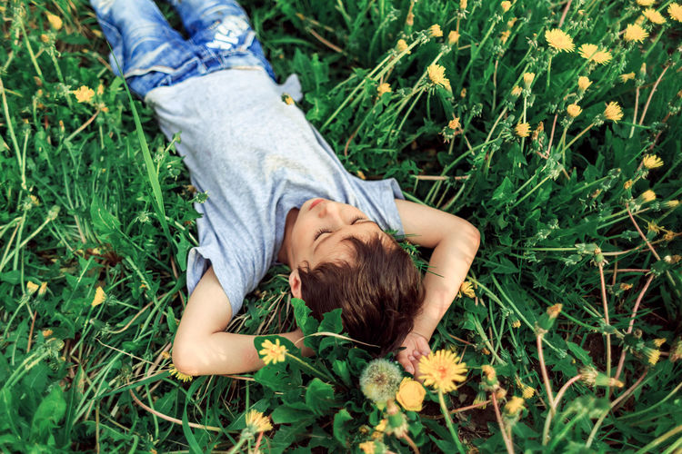 High angle view of boy lying on grassy field