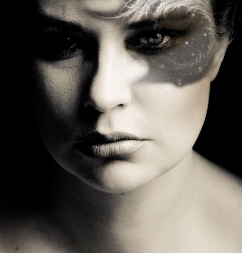 Close-up portrait of serious woman with face paint against black background