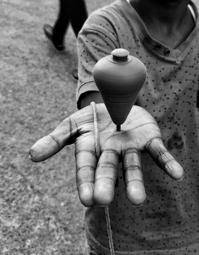 Midsection of boy showing spinning top on hand