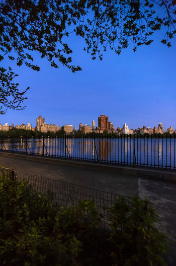 Central Park Central Park Reservoir Central Park Reservoir At Sunset Facing 5th Avenue Scenic Cityscape Reflections
