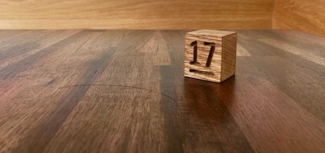 Seventeen Wood - Material Table Text High Angle View Brown No People Indoors  Toy Block Wood Capital Letter Western Script Still Life Communication Day Number Flooring Hardwood Floor Sunlight Single Word Single Object