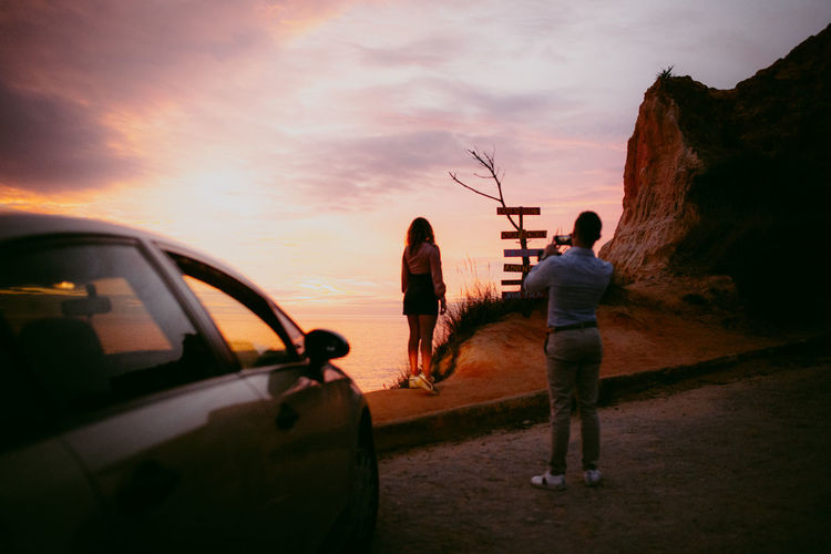 Rear view of people standing by car against sky during sunset