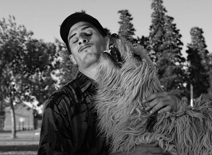 Man playing with hairy dog in park