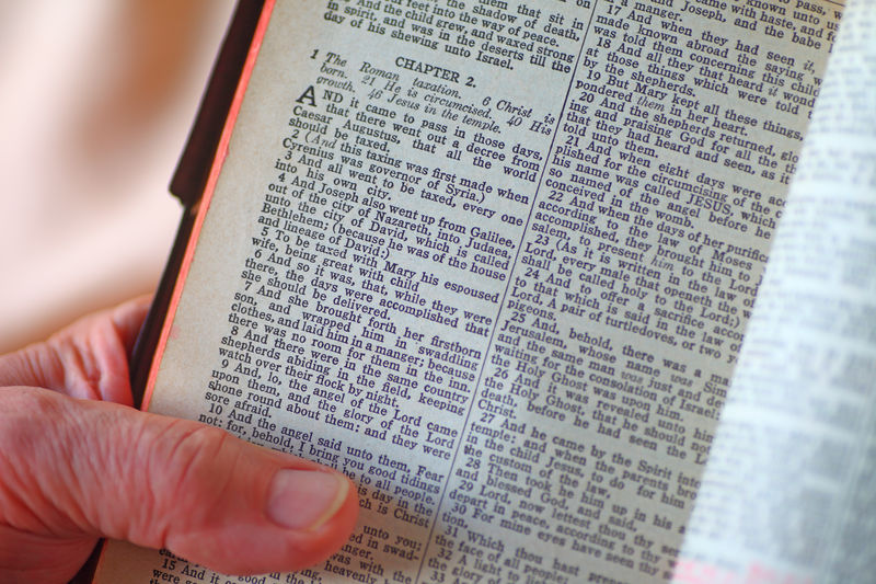 Man with Bible open to Luke, chapter 2 Publication Paper Book Text Reading Indoors  Close-up Communication Studying One Person Holding Belief Christianity Religion Holy Book Bible Verses Man Spiritual Natural Light Point Of View Christmas Story Words Scriptures