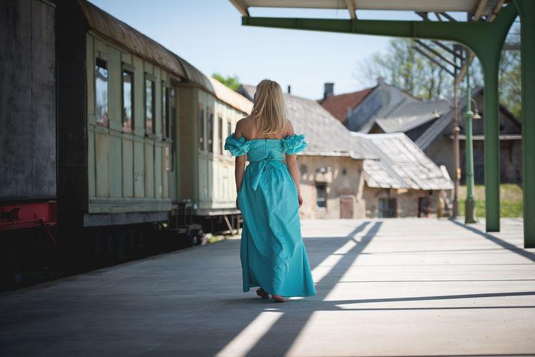 Rear view of woman walking on railroad station platform by train