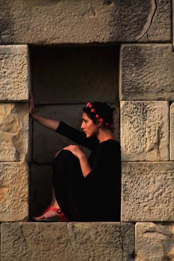 Side view of young woman sitting amidst walls