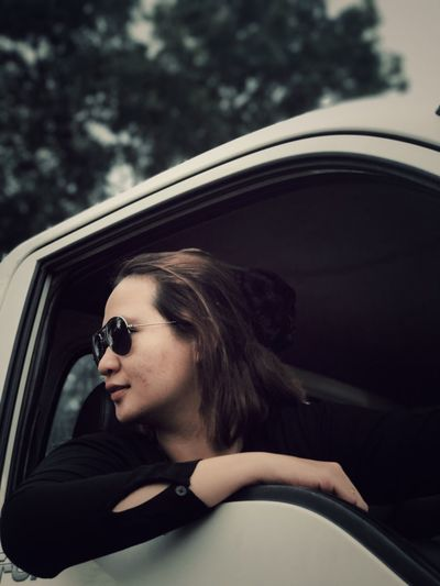 Woman in sunglasses looking through window of car