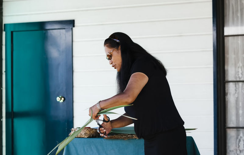 Maori woman cutting flax for basket weaving in Rotorua, New Zealand. Adult Adults Only Woman One Woman Only Mature Women One Mature Woman Only Basket Close-up Communication Art And Craft Craft Cultures Cutting Polynesian Females Flax New Zealand Flax Human Hand Hand Happiness Homemade Handmade DIY Indigenous  Leaf Looking Down Concentration Maori Maori Culture Material Mature Adult New Zealand North Island People Plant Portrait Preparation  Basket Weaving Reed - Grass Family Rotorua  Scissors Summer Sunglasses Talking Tradition Tribal Waist Up Weaving Working Woven One Person Real People Side View Casual Clothing Standing Three Quarter Length Day Wall - Building Feature Holding Architecture Built Structure Lifestyles Building Exterior Leisure Activity Hair Looking Outdoors Hairstyle Profile View