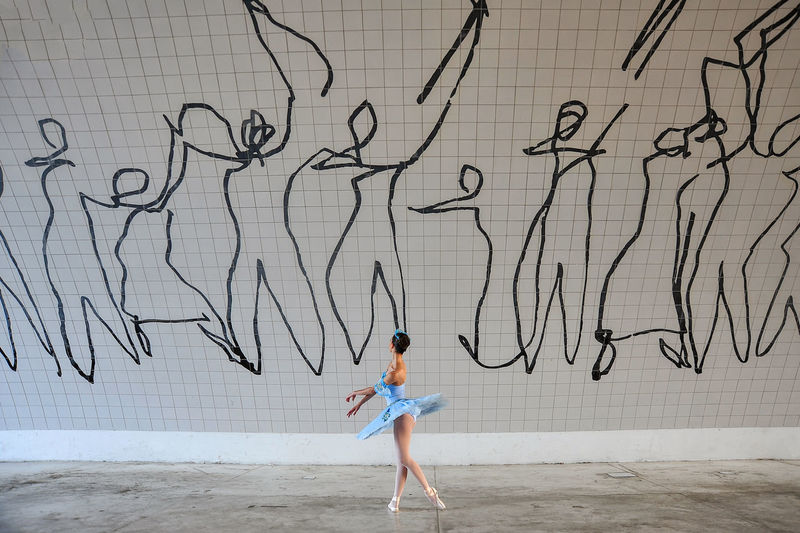 Side view of woman dancing against graffiti wall