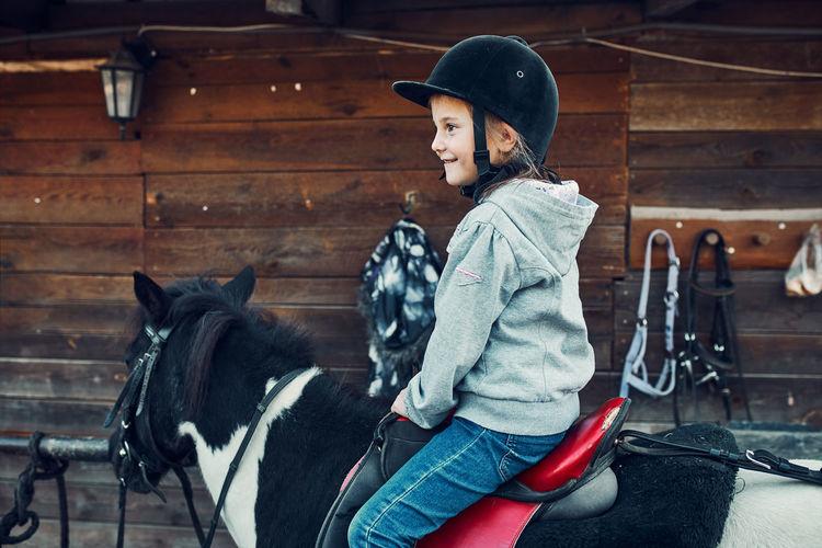 Little smiling girl learning horseback riding. 5-6 years old equestrian in helmet having fun riding