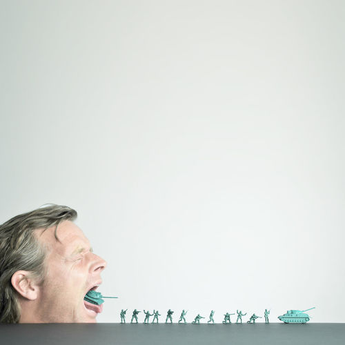 Mature man with toy tank in mouth by figurines against white background