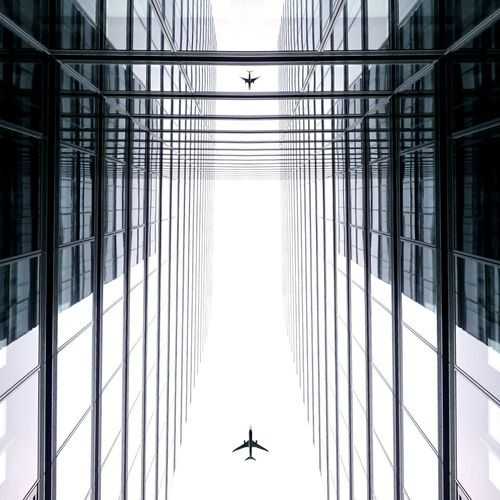 Low Angle View Of Airplanes Above Tall Buildings
