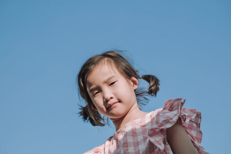 Portrait of girl against clear blue sky