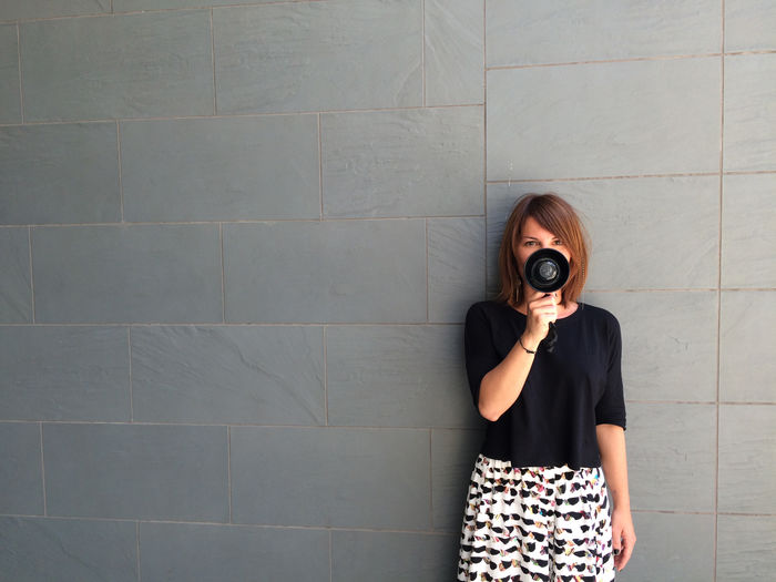 Portrait of woman holding equipment while standing against wall