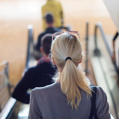 Rear view of woman standing on escalator outdoors