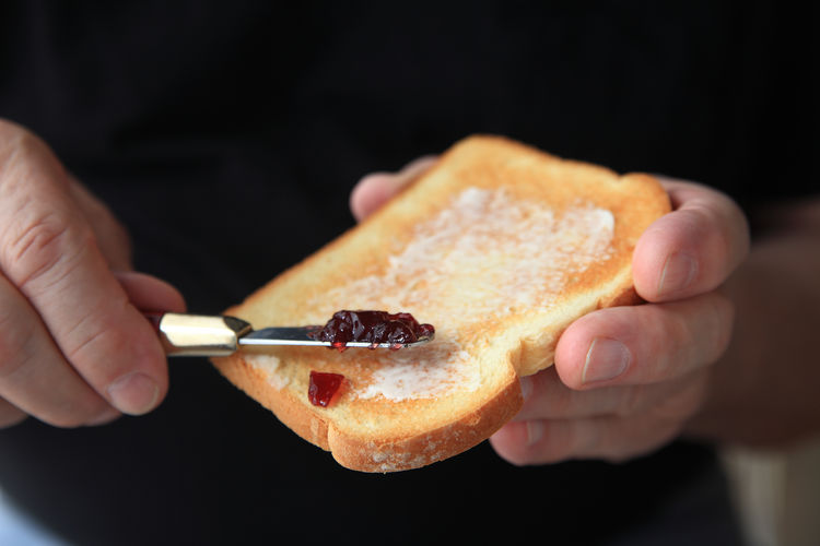 Midsection Of Man Applying Jam On Toasted Bread