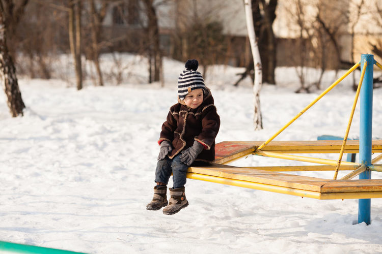 Full length of boy on snow covered landscape during winter
